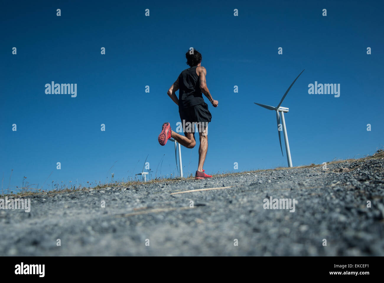 Mid adult man jogging up a hill towards wind turbines - Stock Image