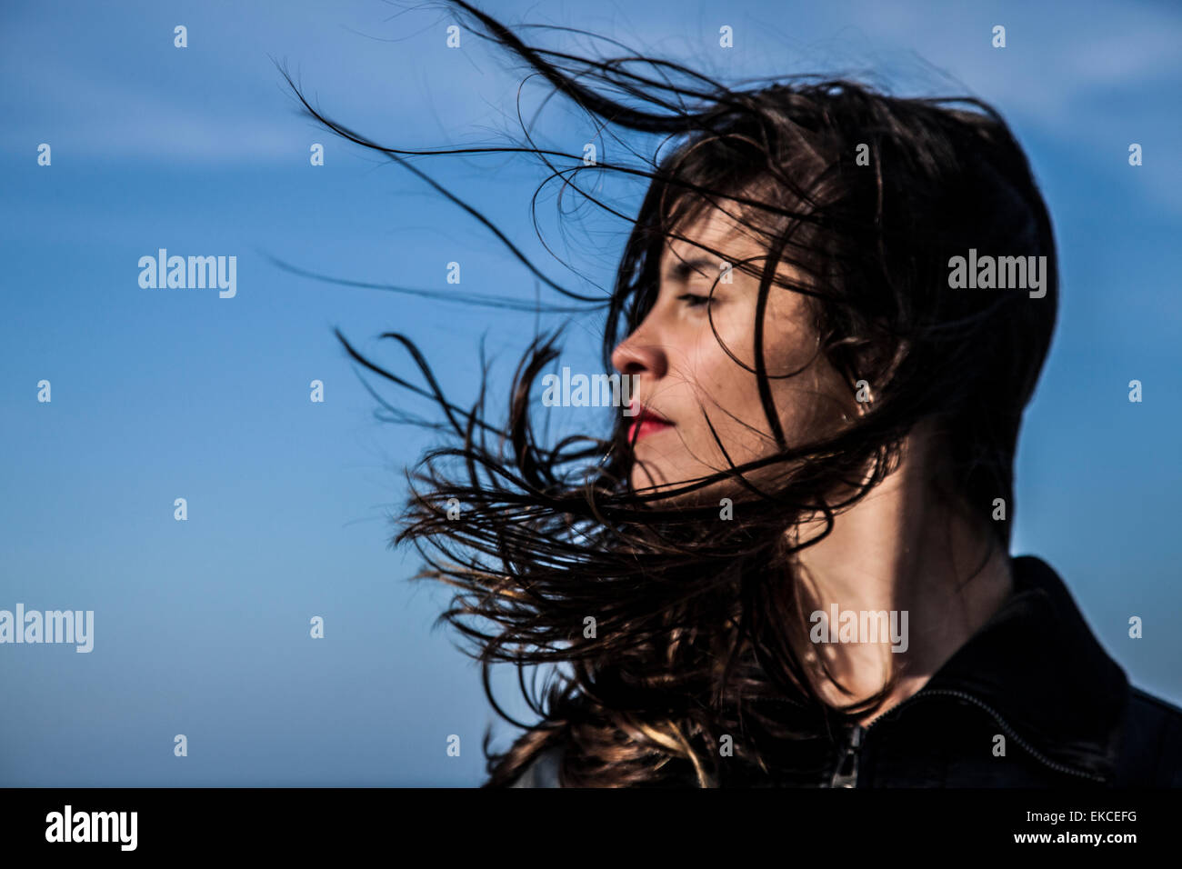 Young woman looking sideways with hair blowing in the wind Stock Photo