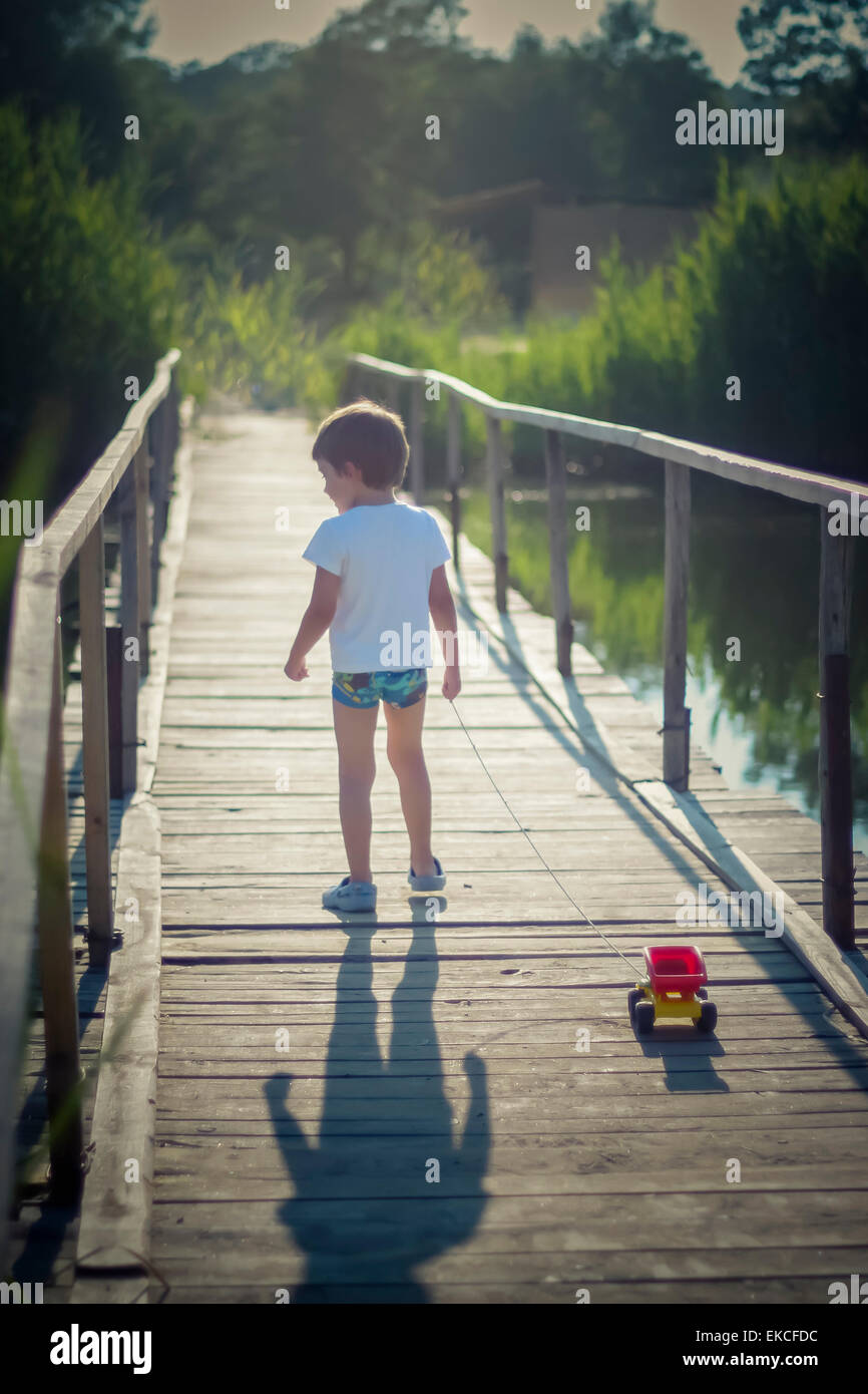 Boy pulling a toy truck across a bridge Stock Photo