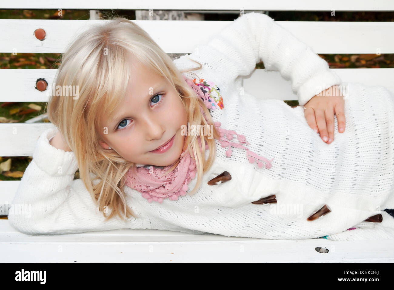 Young girl lying on a bench - Stock Image