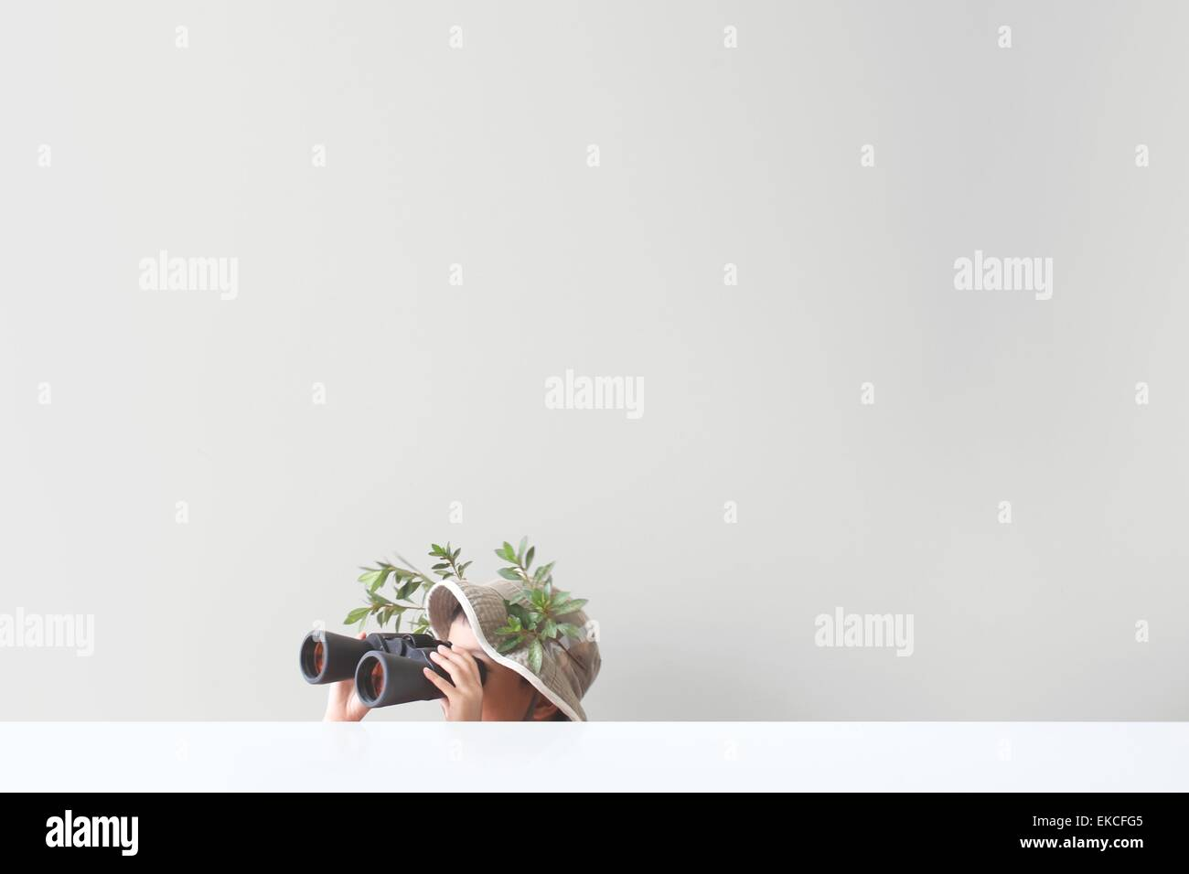 Boy looking through binoculars with some leaves and tree branches stuck on his safari hat - Stock Image