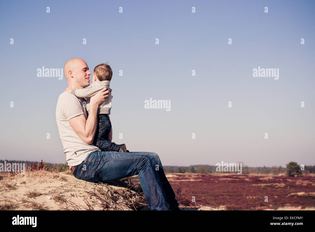 Father holding his son at the beach - Stock Image