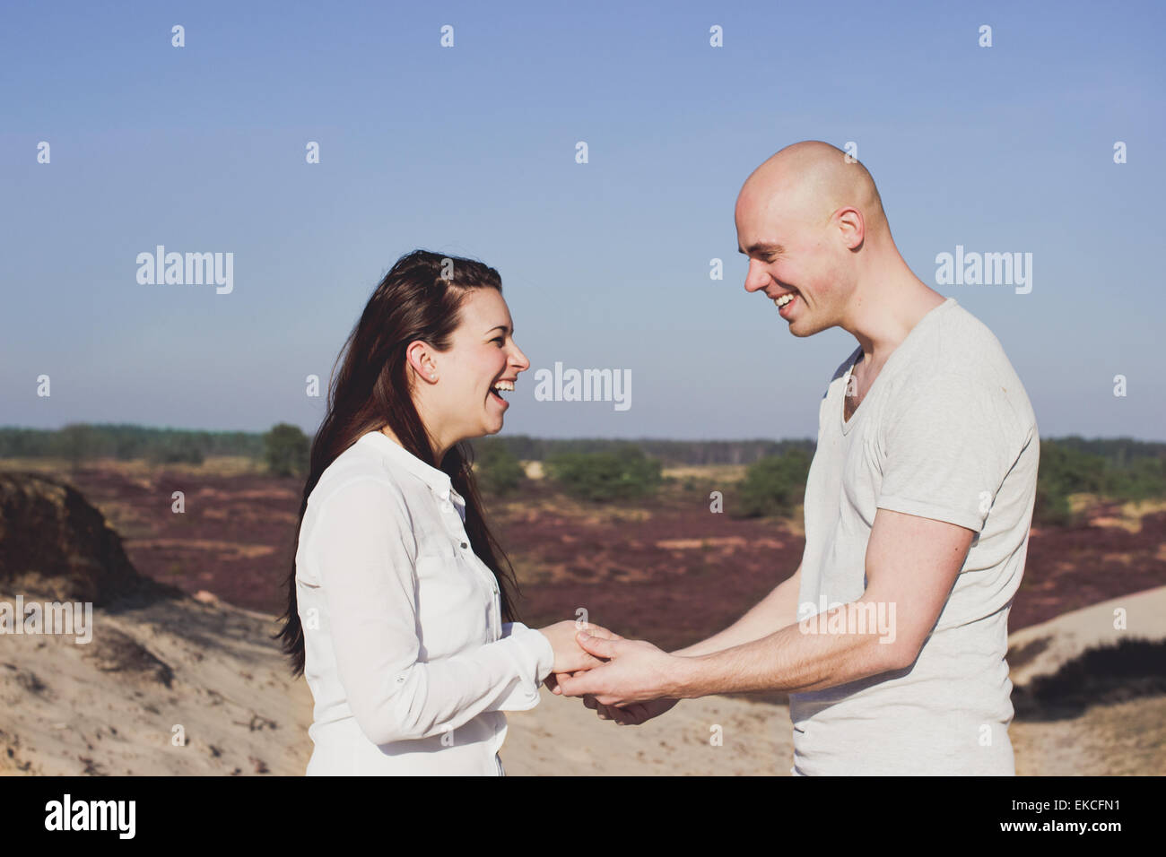 Portrait of a couple holding hands, laughing - Stock Image