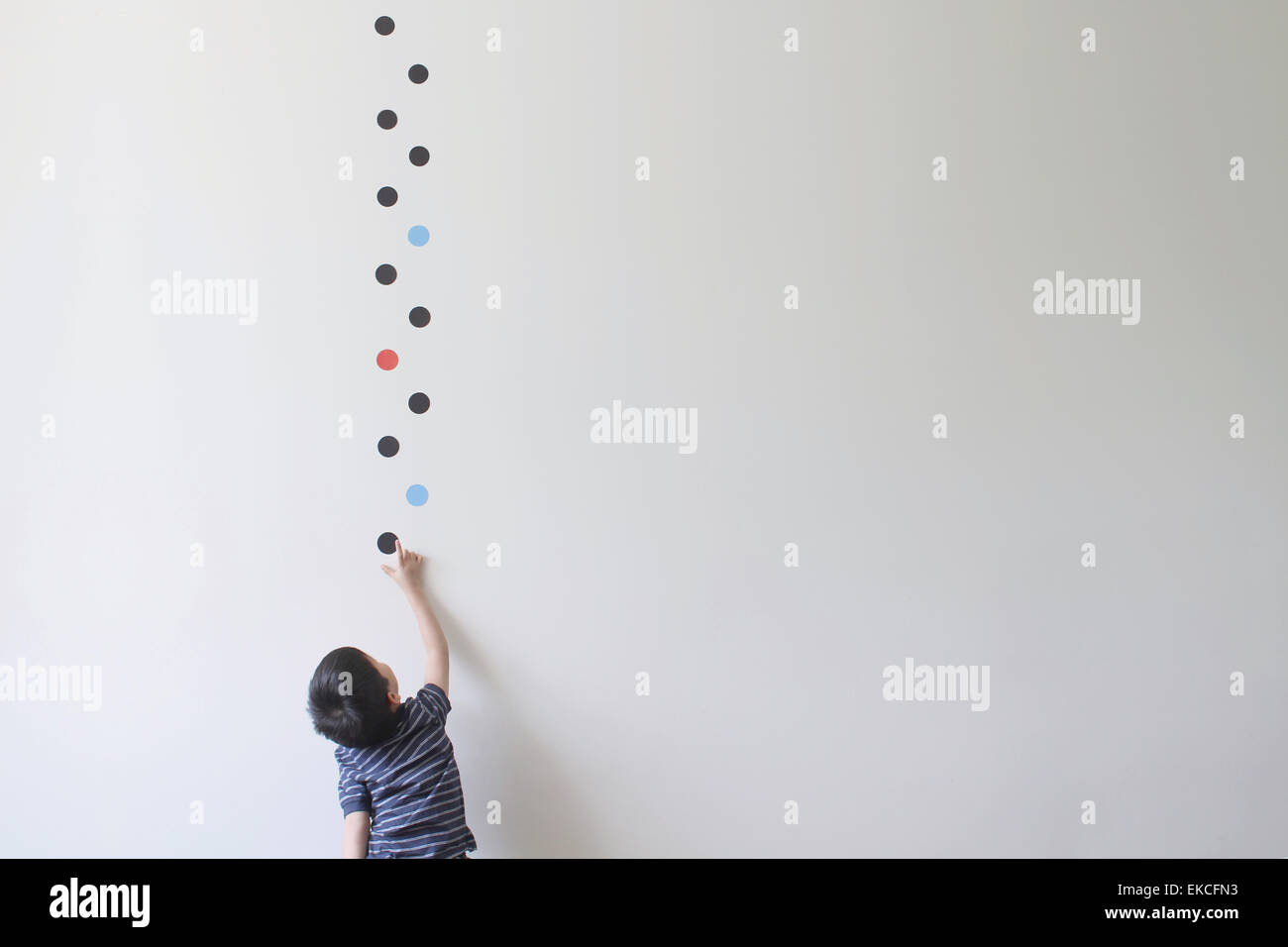 Boy trying to pick one of the dot patterns off the wall Stock Photo