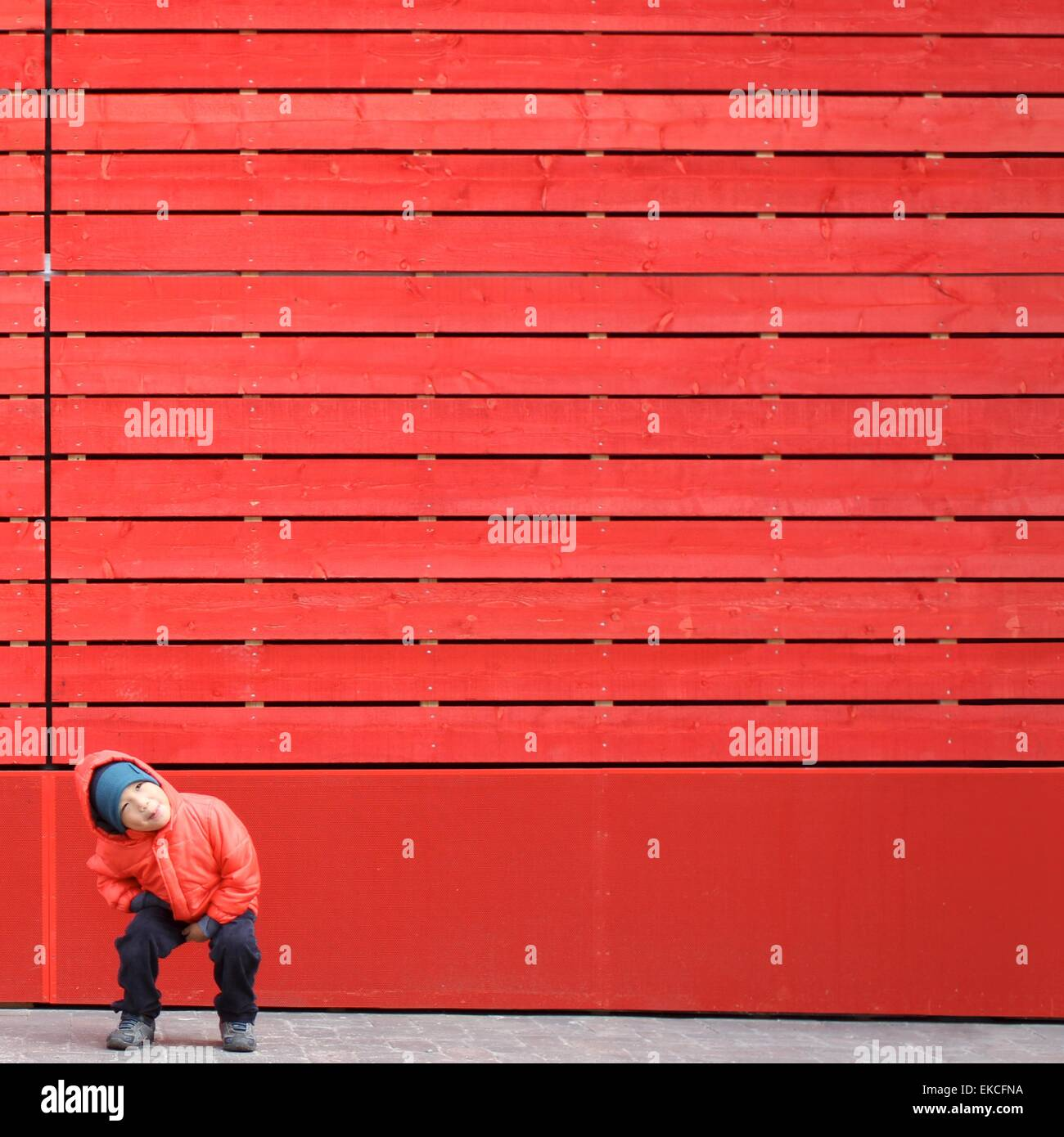 Boy in red playing in front of a red wall - Stock Image