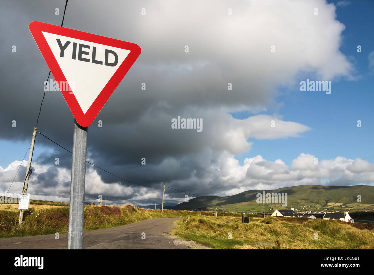 Give way sign with dark clouds in Ireland - Stock Image
