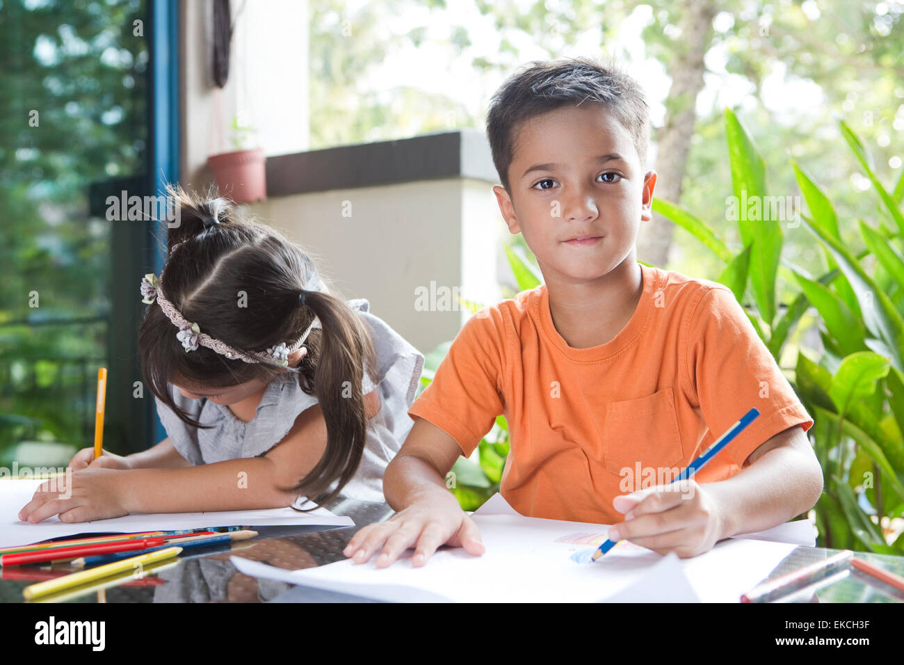 Pan asian boy sitting next to his younger sister enjoying a coloring book activity - Stock Image