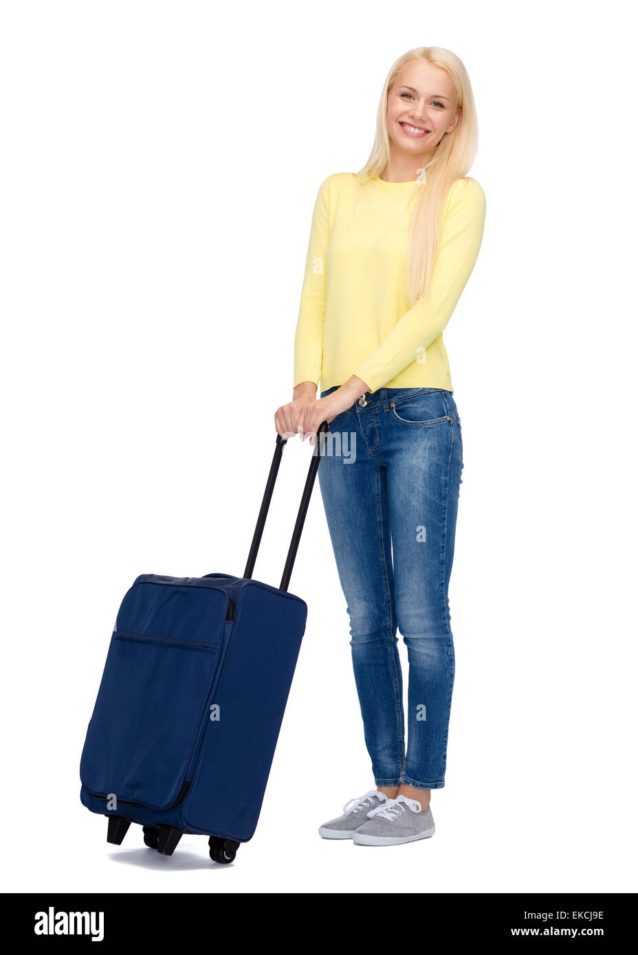 smiling young woman with suitcase - Stock Image