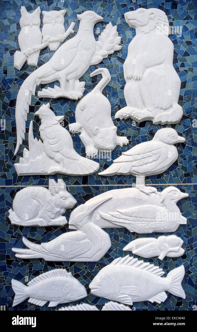 This 1970s artistic creation of white marble carvings of animals, birds and fish against a mosaic of colored tiles - Stock Image