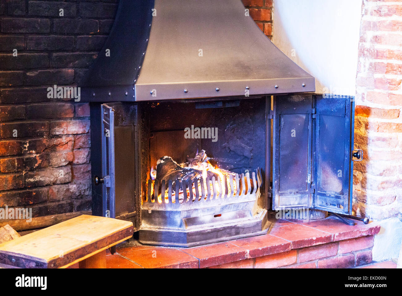Log burner burning logs door open fire heat warmth warming room Norfolk UK England - Stock Image