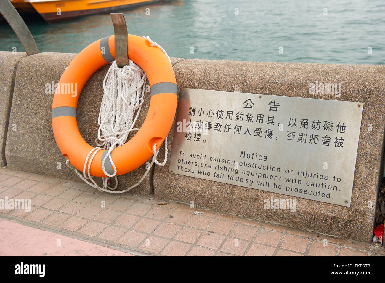 Lifesaver mounted on curb of promenade with instructions on safety, Hong Kong - Stock Image