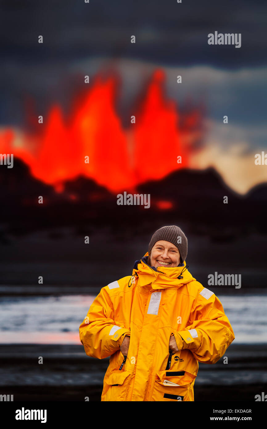 Woman standing by Glowing lava from the eruption at the Holuhraun Fissure, near the Bardarbunga Volcano, Iceland - Stock Image