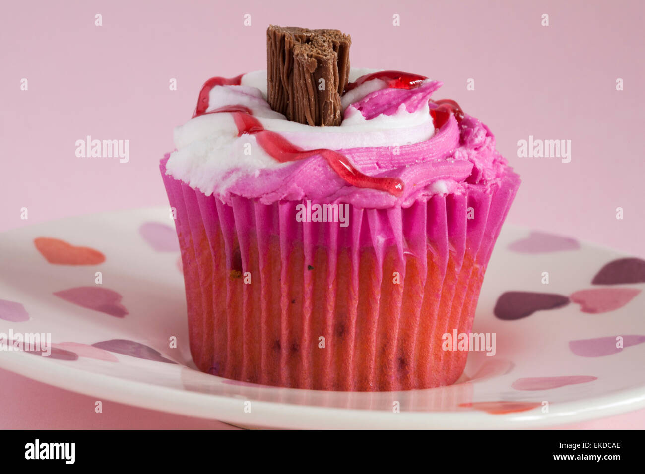 Raspberry Ripple cupcake with chocolate flake on hearts plate set on pink background - Stock Image