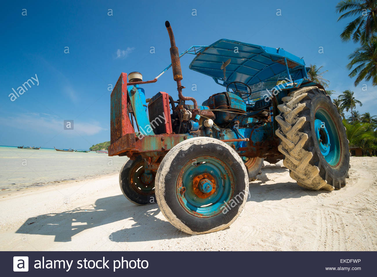 Blue tractor on a beach : used to carry people and goods from and to the boats at low tide - Stock Image