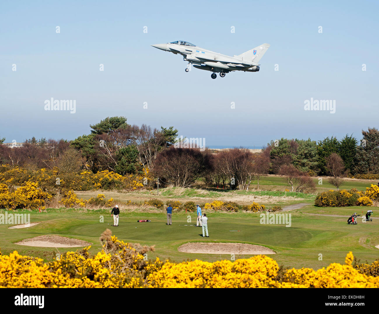 Golfers out of their local course at Lossiemouth while Eurofighter  aircraft come into land at the RAF Base.  SCO - Stock Image