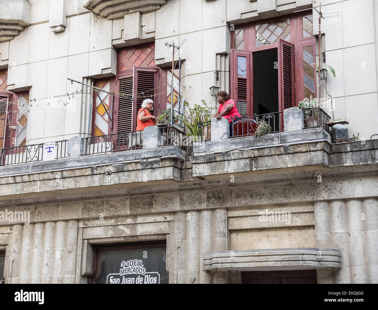 Two female adult Cuban neighbors, both wearing red tops, talking while on the balconies of their second story apartments. - Stock Image