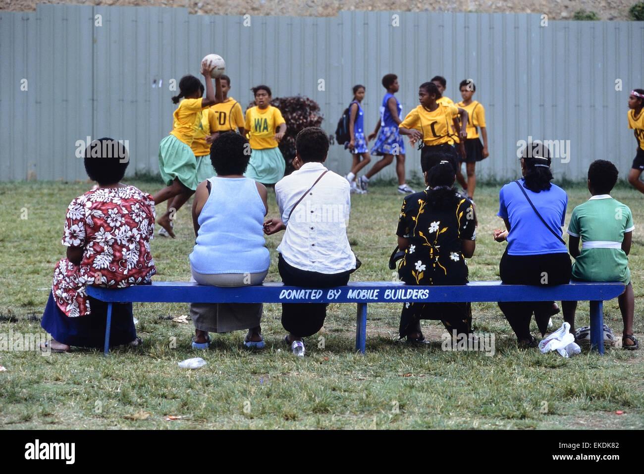 School children and parents watching a girls netball match at Churchill Park. Lautoka. Fiji. South Pacific. - Stock Image