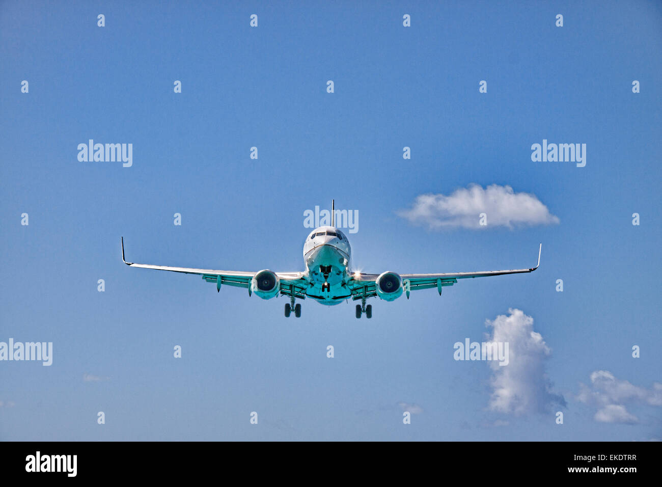 A Boeing 737 Jet of United Airlines Approaching Princess Juliana International Airport over Maho Beach on St. Marten - Stock Image
