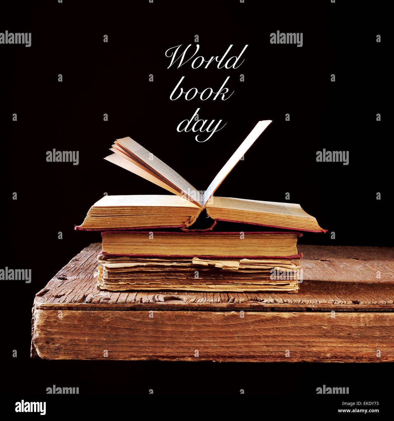 some old books on a rustic wooden table and the text world book day written in white on a black background - Stock Image