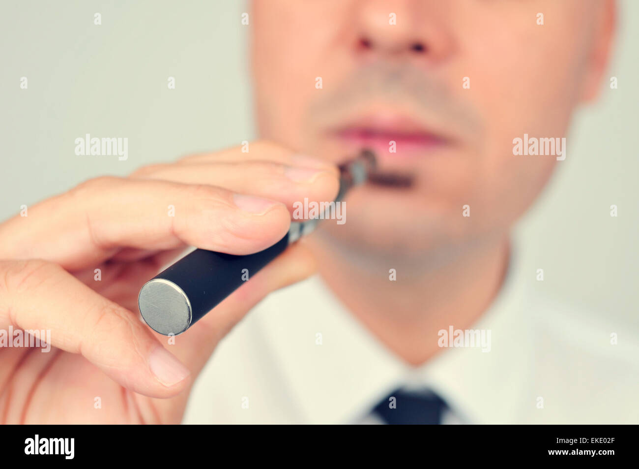 closeup of a young caucasian man wearing a white shirt and black tie vaping with an electronic cigarette - Stock Image