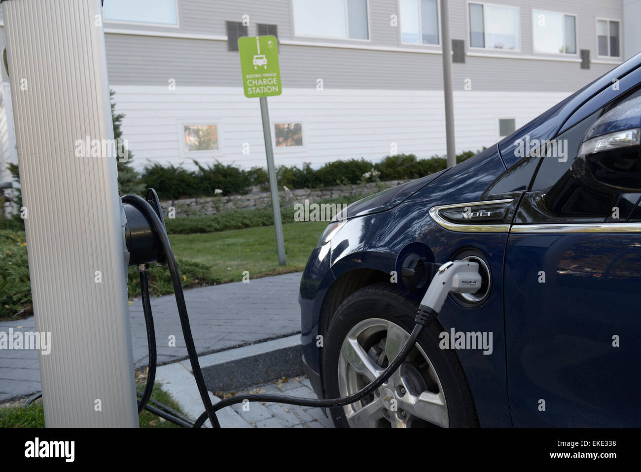 Electric car charging at a hotel parking lot charging station - Stock Image
