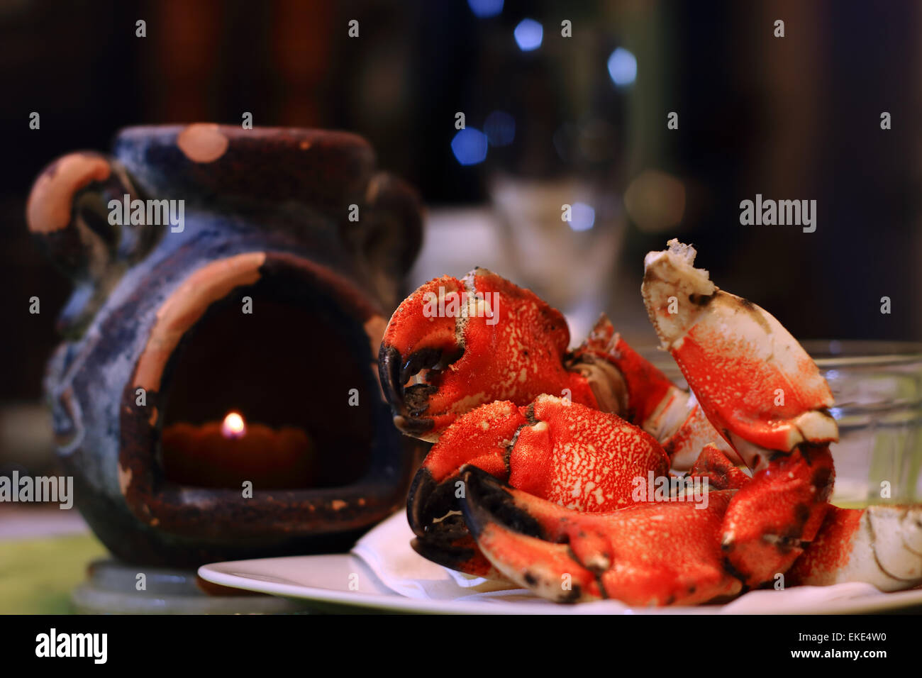 Jonah crab claws on a plate, with candle light and defocsed wine glass in fine dining restaurant. Jonah crabs, aka - Stock Image