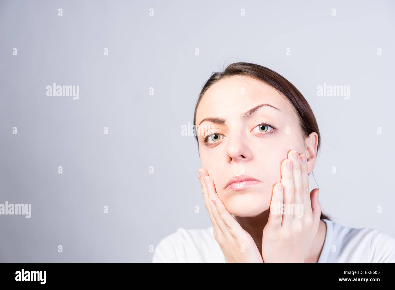 Close up Serious Young Woman Touching her Face with Two Hands While Looking at the Camera. Captured in Studio with - Stock Image