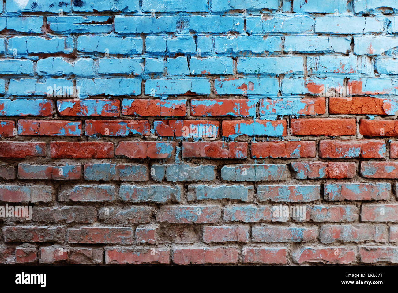 Old red brick wall half painted in bright blue color a lot of copyspace background Stock Photo