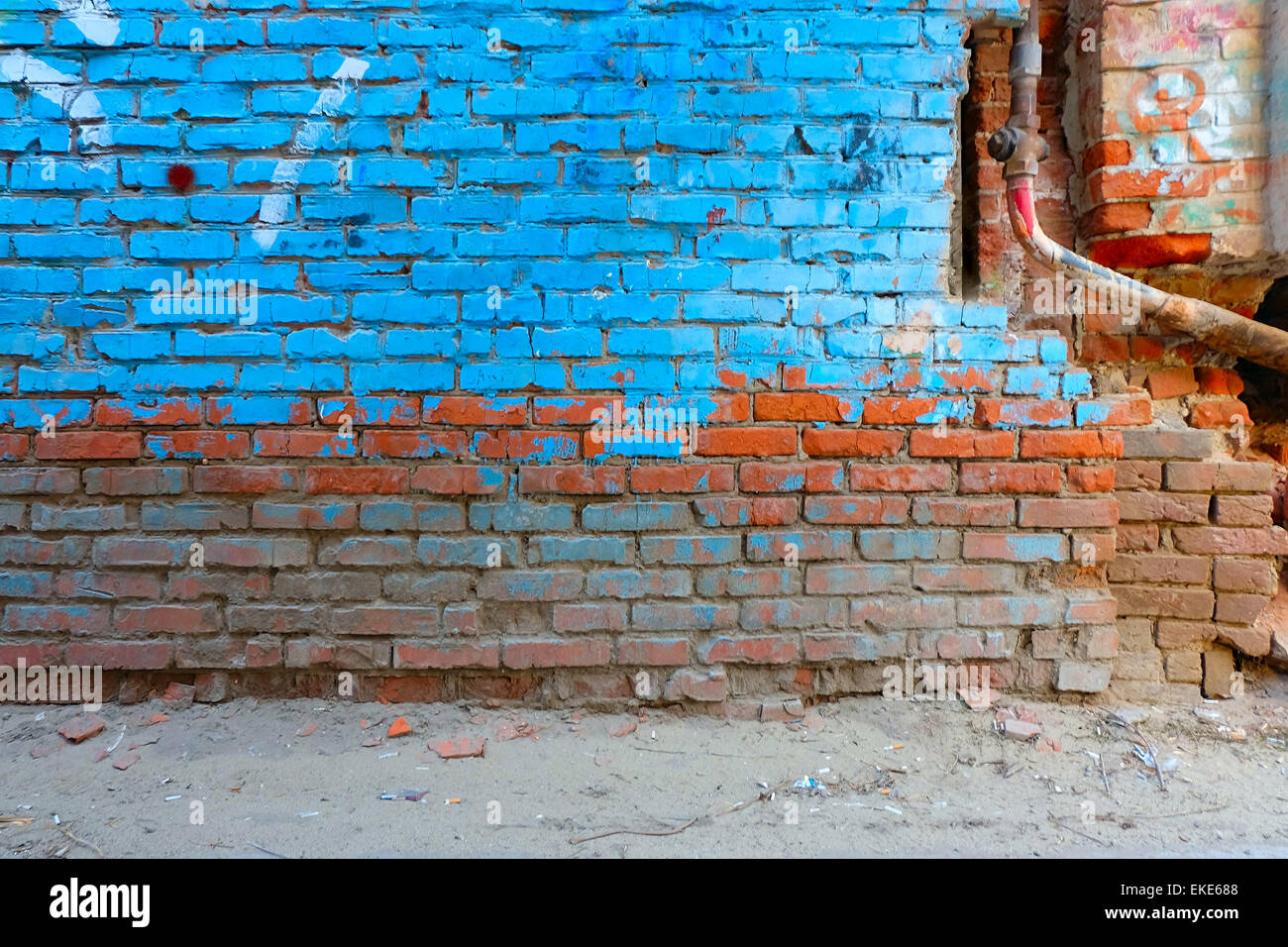 Old Brick Wall Half Painted In Bright Blue Color And Rusty