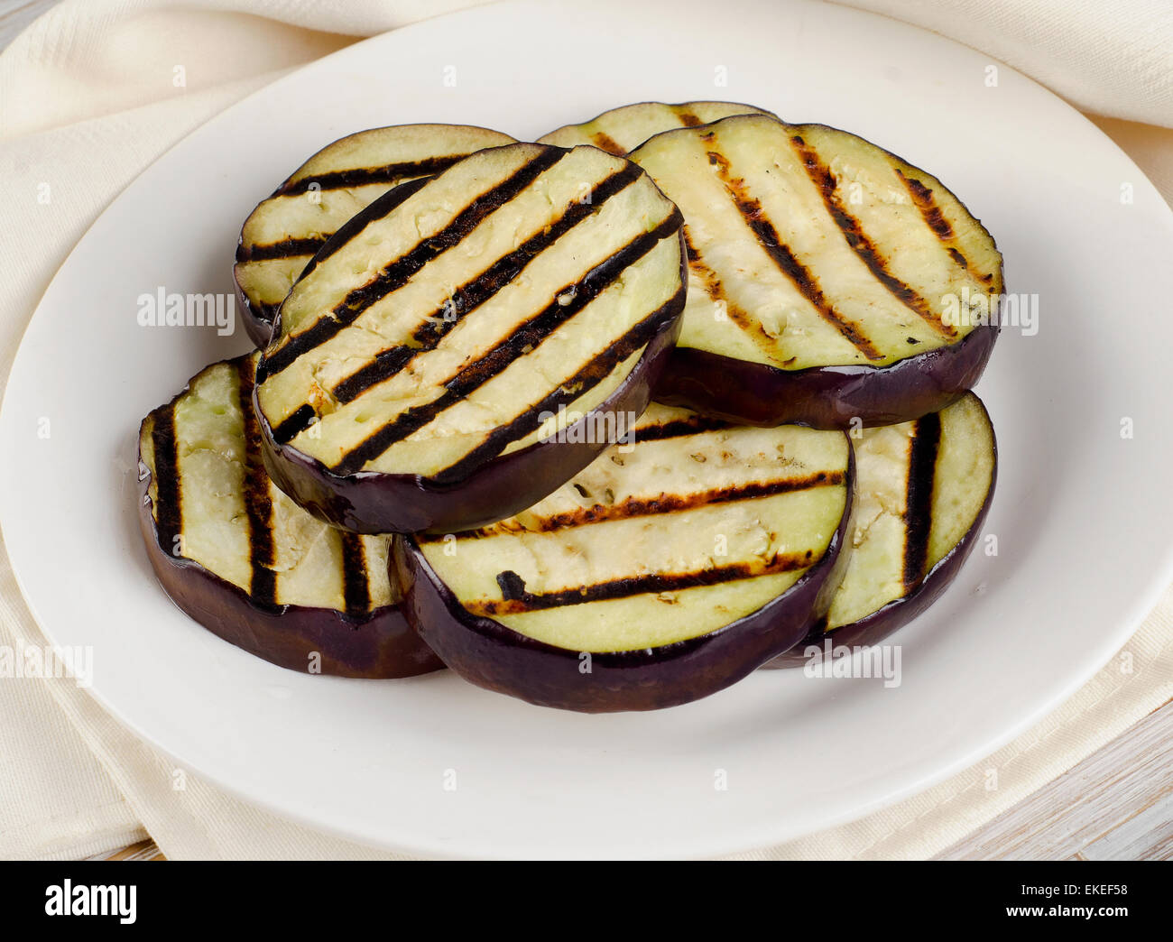 Grilled eggplant  on a white plate. Selective focus - Stock Image