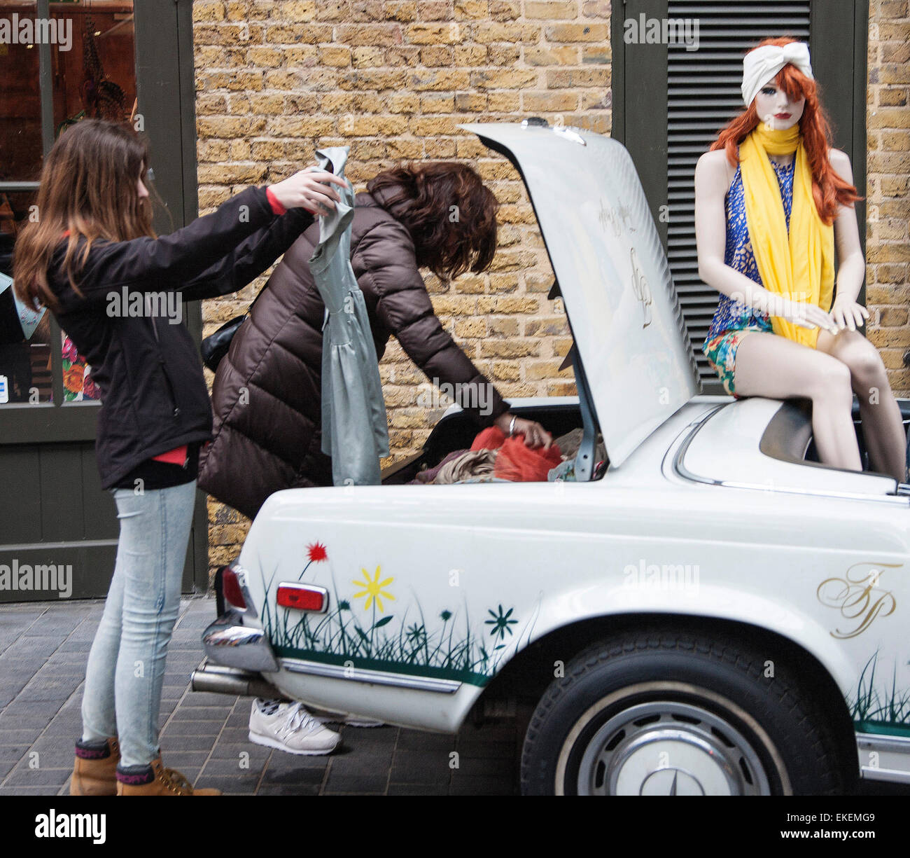 Ladies looking at clothes out of a car boot - Stock Image