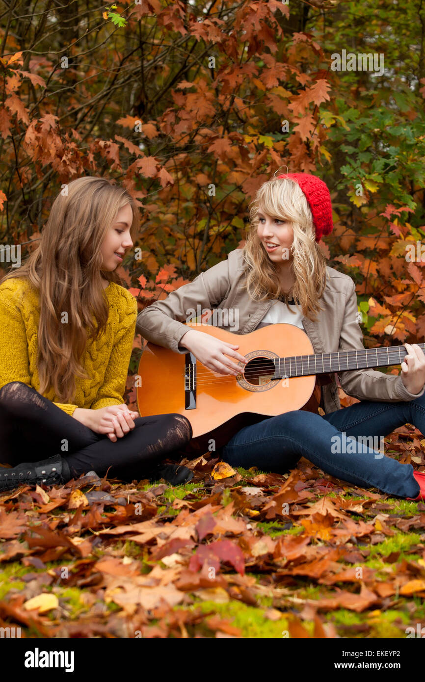 Girlfriends having a nice time with a guitar - Stock Image