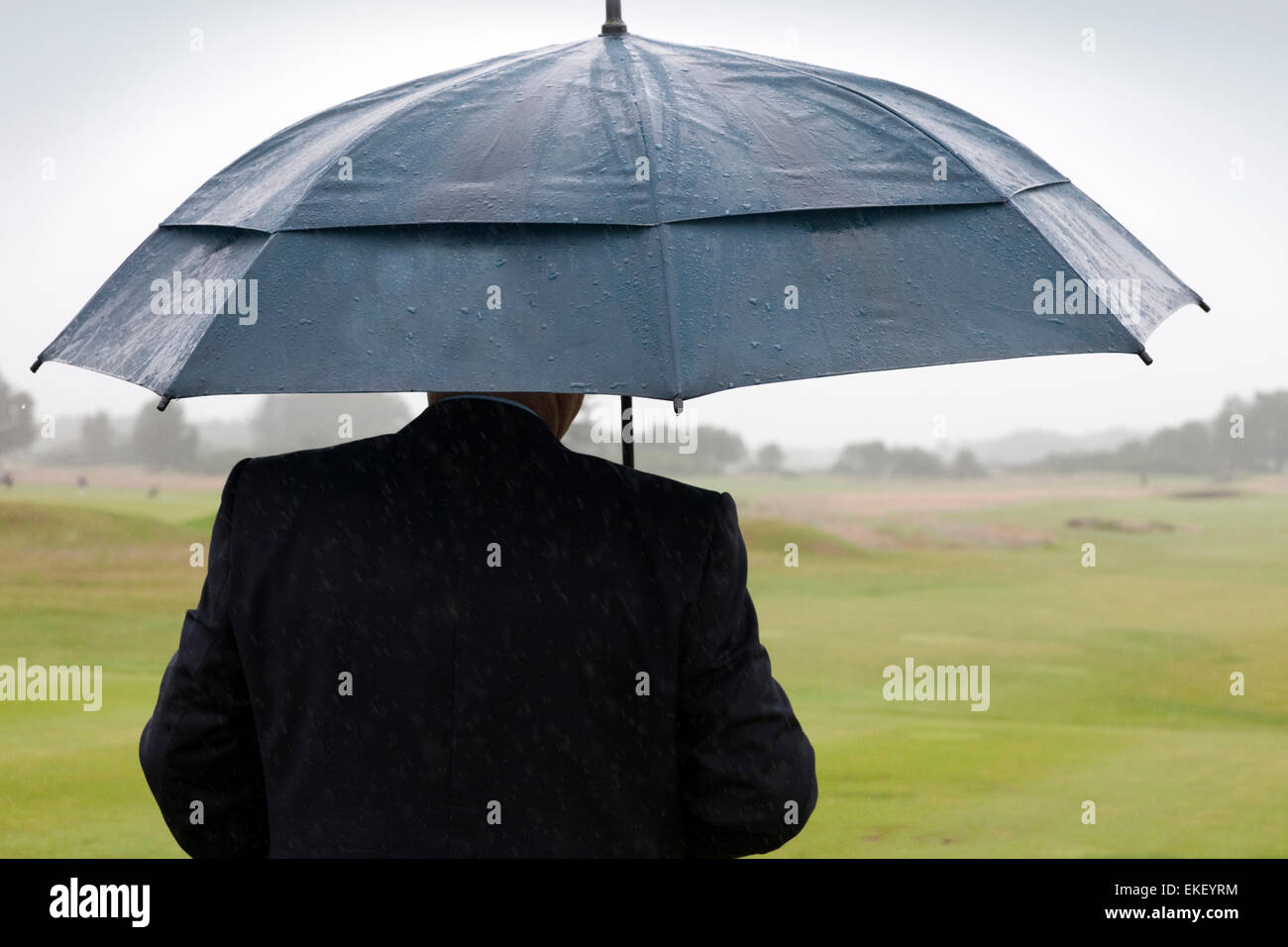Golfer sheltering under an umbrella, looking out onto a golf course while it's raining - Stock Image
