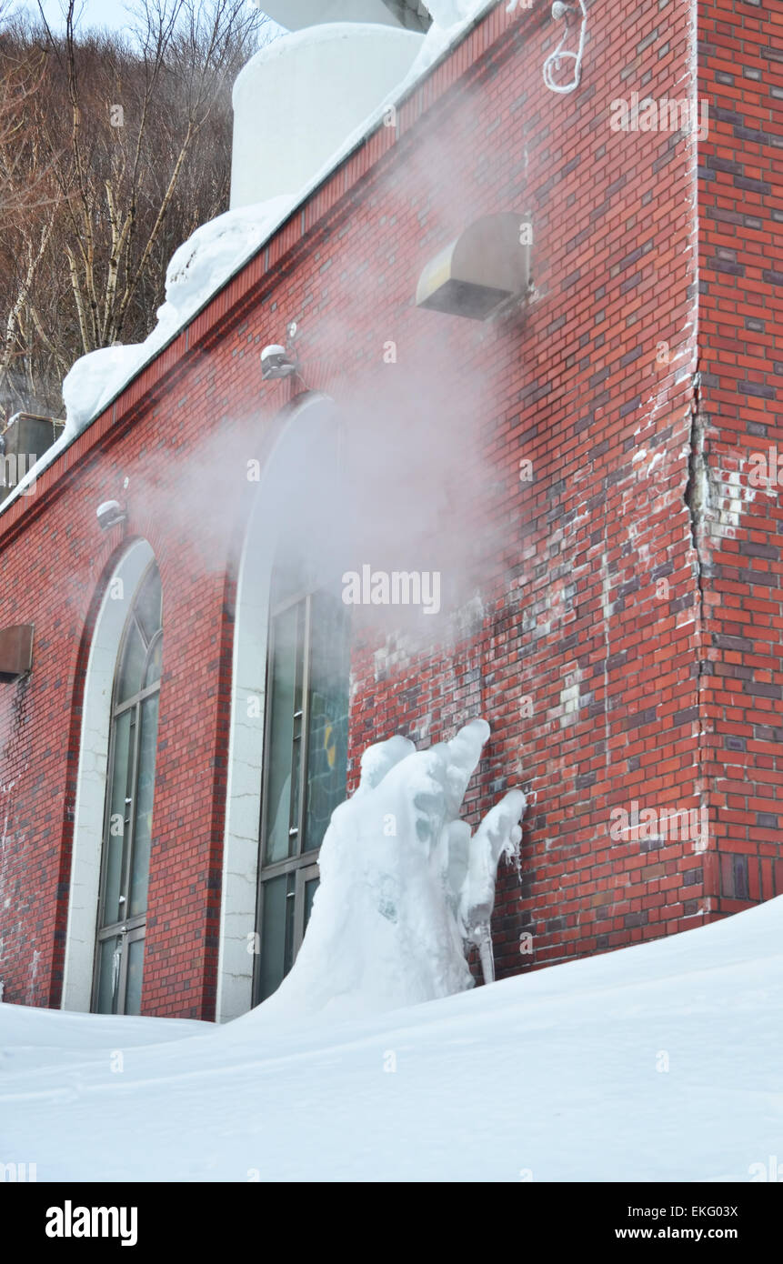 Hand-shaped ice crawls on the red brick wall Stock Photo