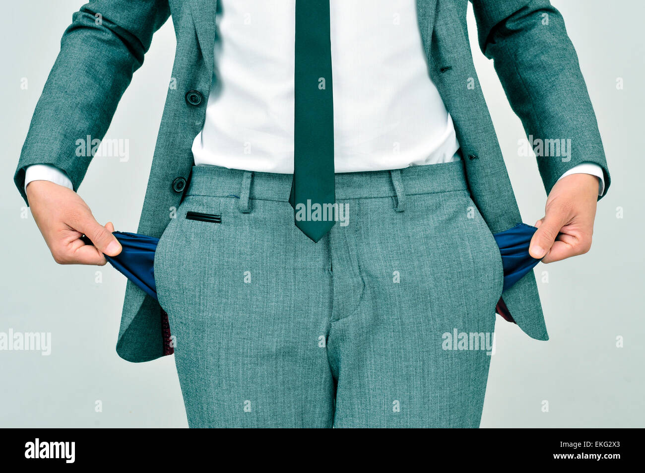 broke businessman wearing a gray suit showing his empty pockets - Stock Image