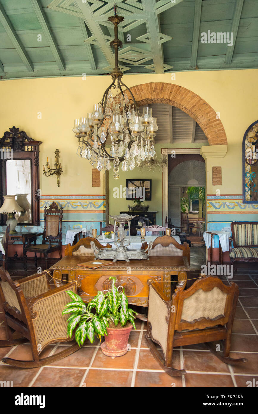 Cuba Trinidad interior detail old antique furniture rocking chairs chandelier ornate decorative walls laid table - Stock Image