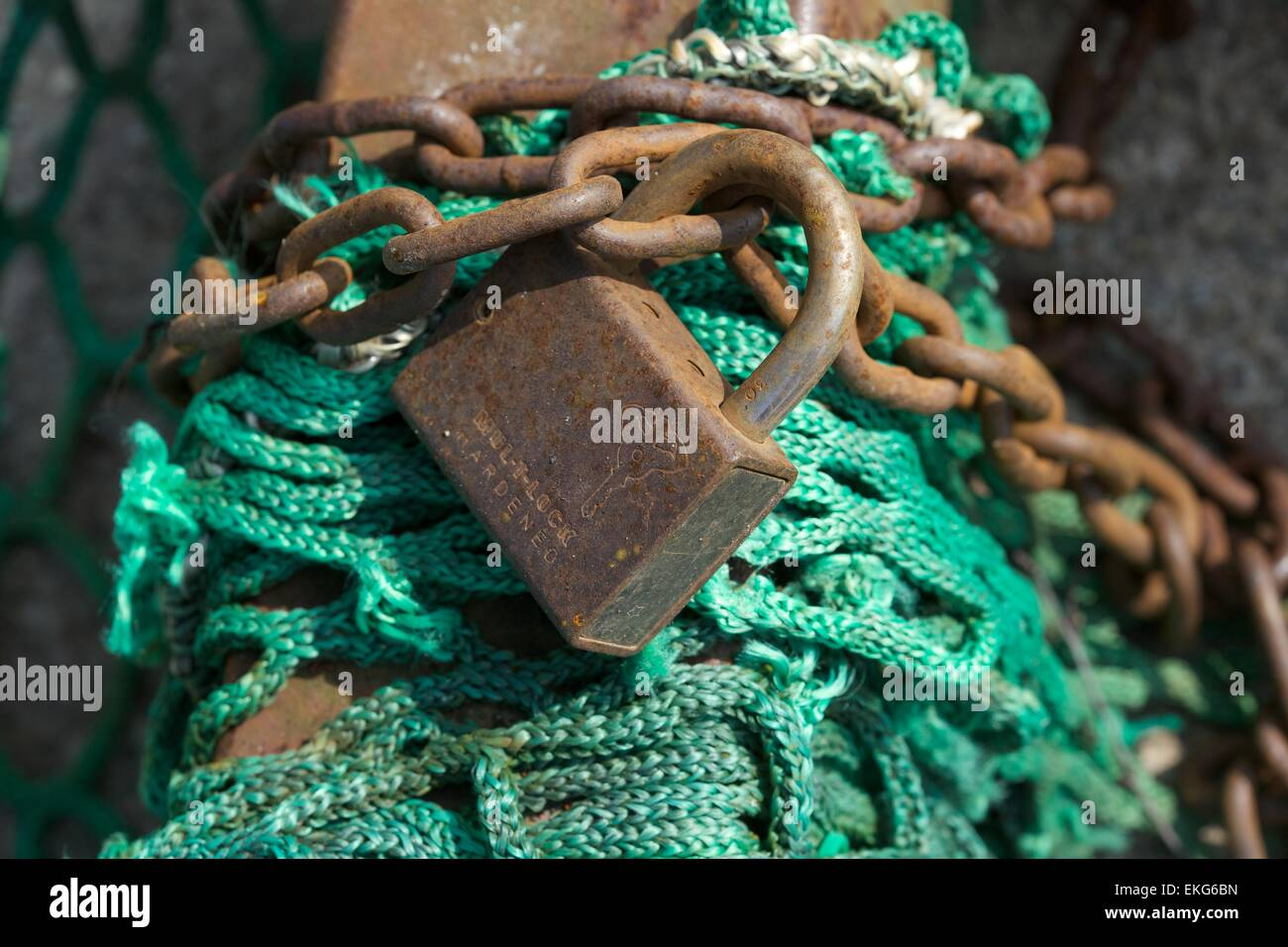 An old padlock on a post with chain and some rope netting - Stock Image
