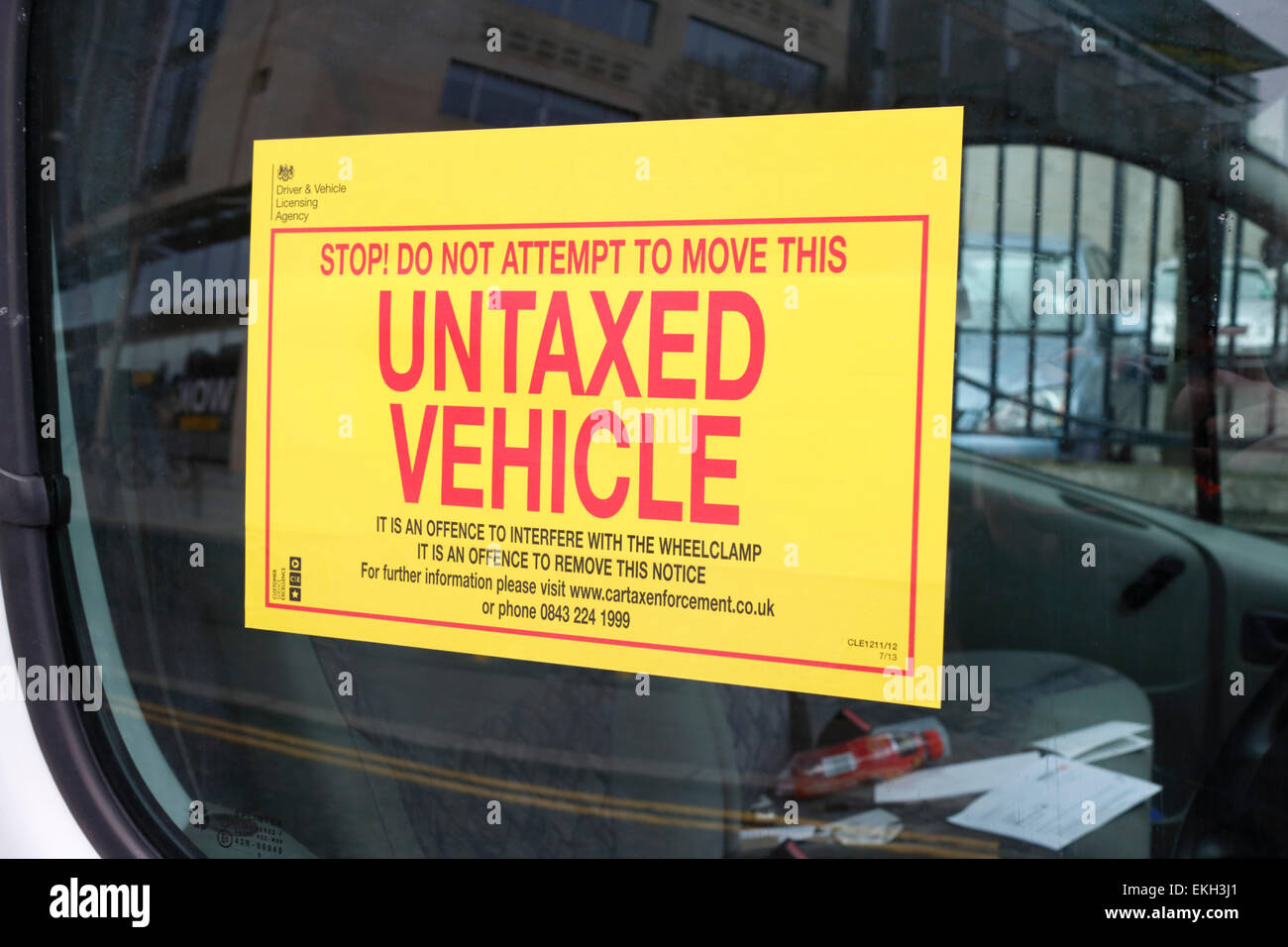 warning sticker attached to window of vehicle clamped for unpaid vehicle tax - Stock Image