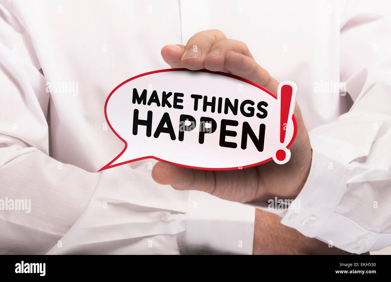 Image of a man hand holding speech balloon with the text make things happen, white shirt. Concept for motivation - Stock Image