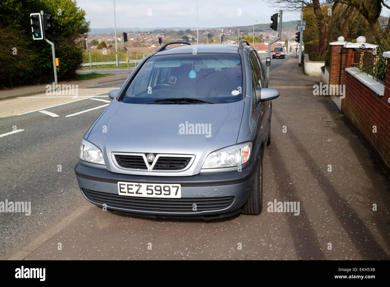 car parked on pavement outside homes in residential suburban street - Stock Image