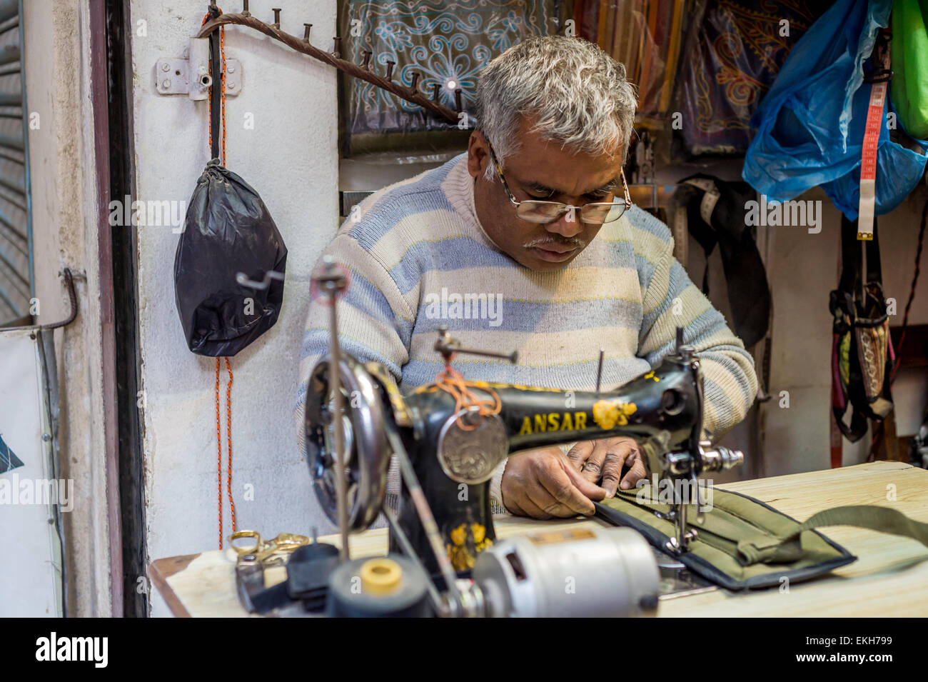 Unidentified Nepali tailor man sewing with old machine in a workshop - Stock Image
