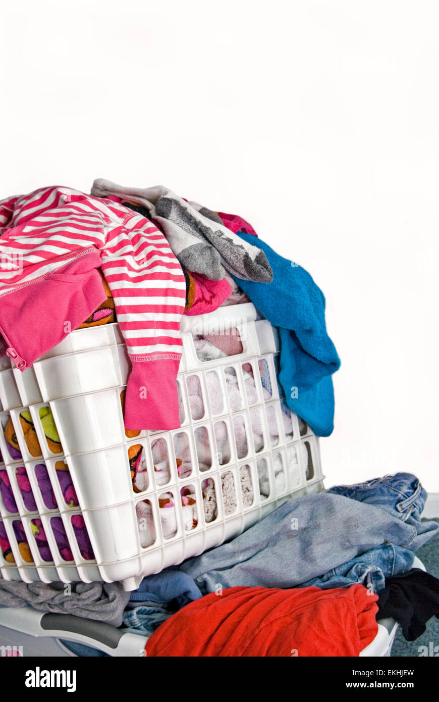 Pile of colorful clothes in a white laundry baskets isolated on white. - Stock Image