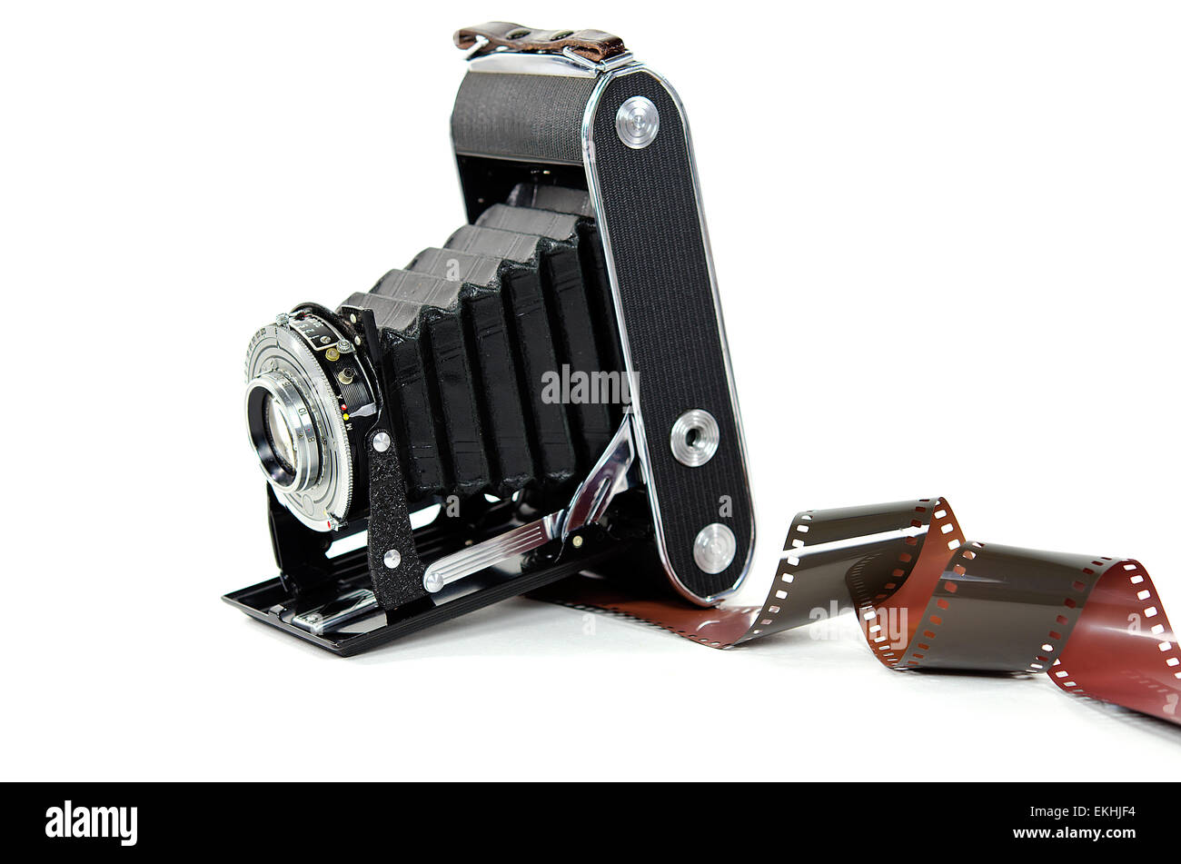 Vintage bellows camera with roll of film isolated on white. - Stock Image