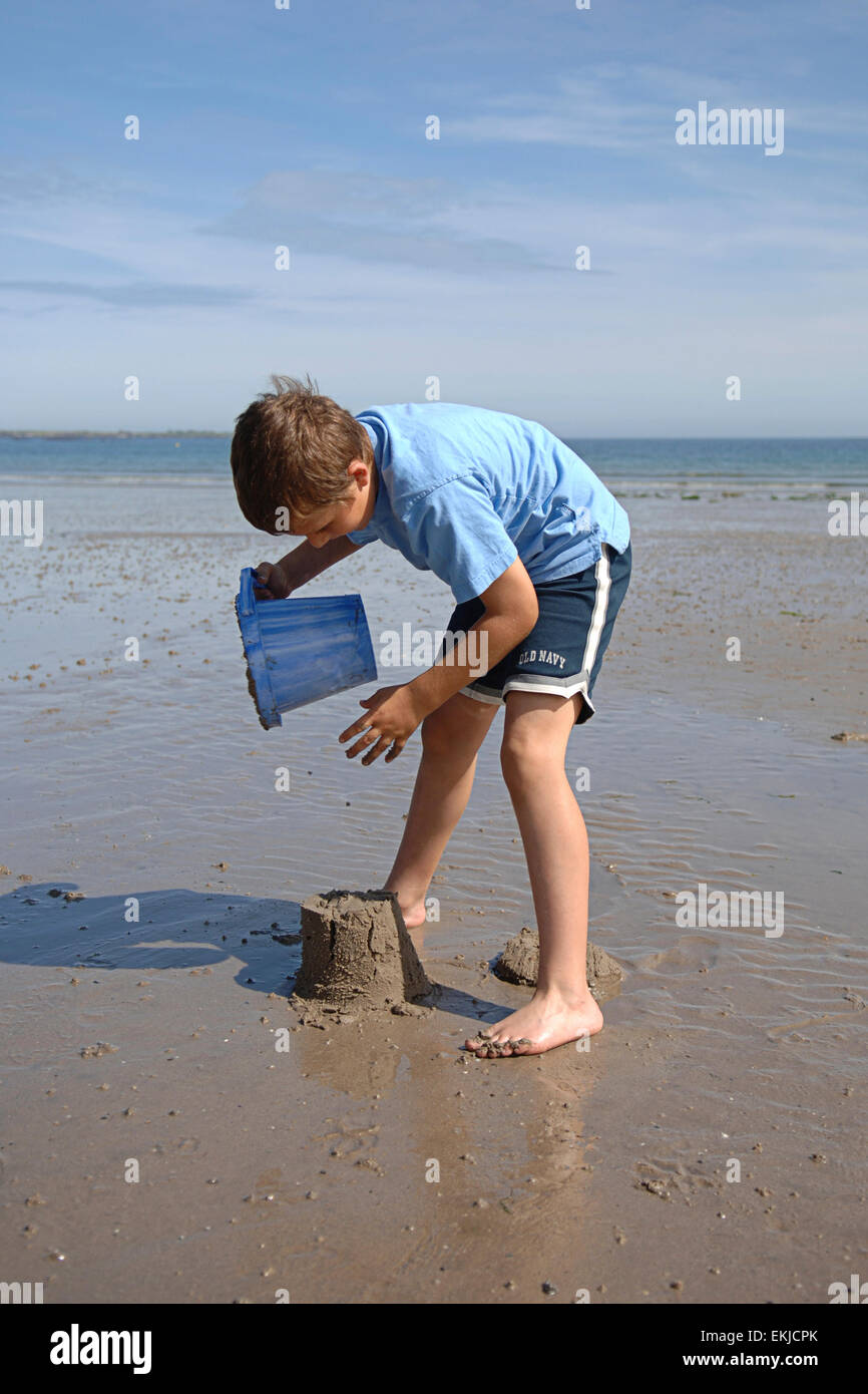 13e1c2fbc Young boy in blue shorts and t-shirt with bare feet making a sand castle on  a beach