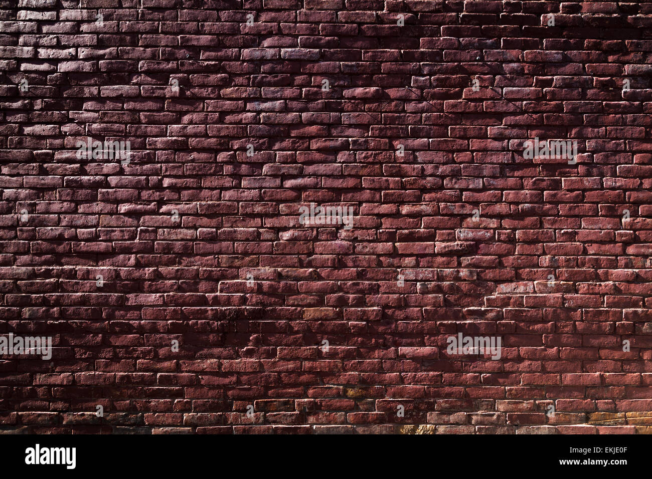 Old Red Brick Wall with Sunlight and Shadows Stock Photo