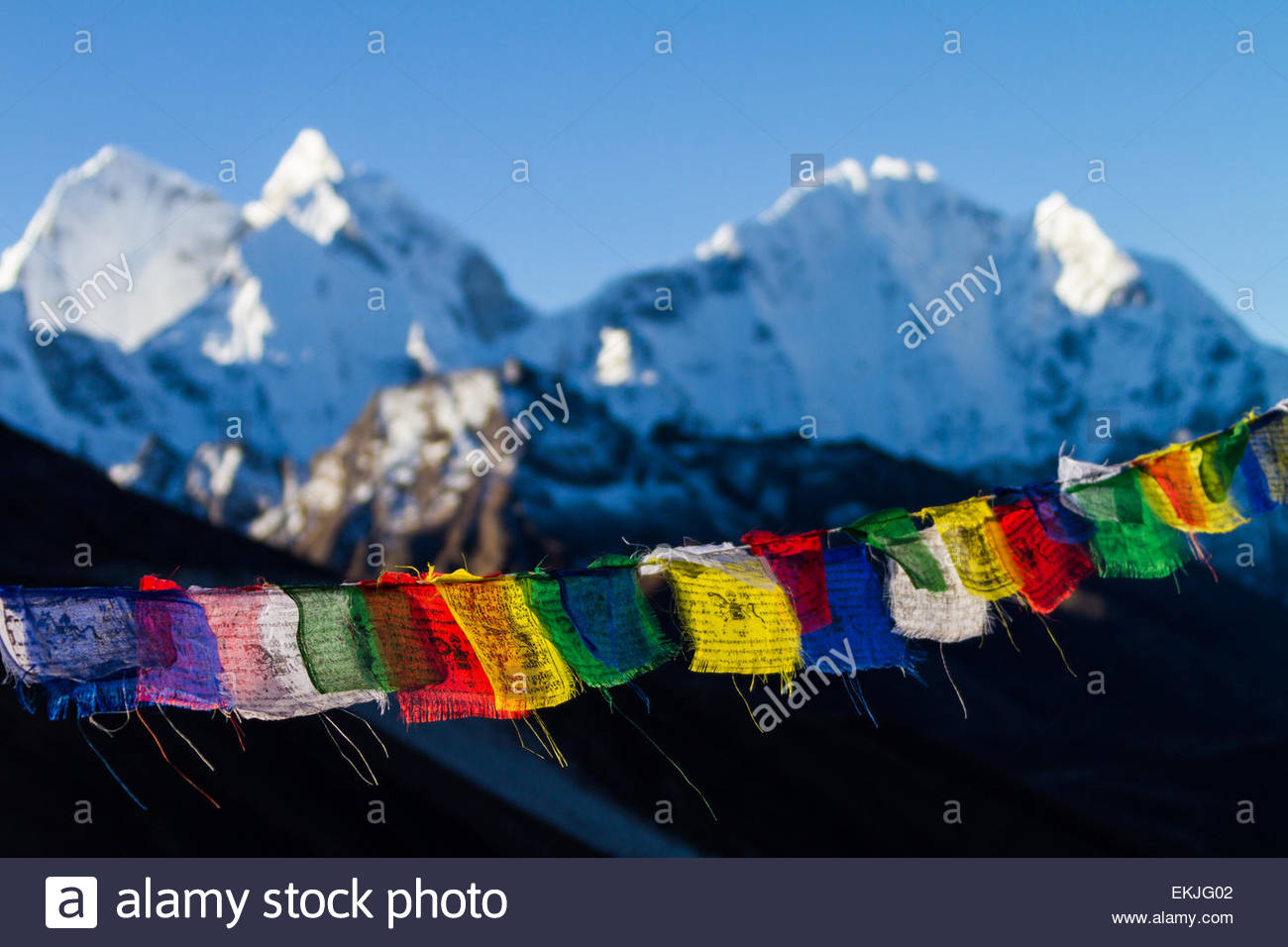 Buddhist prayer flags fly in front of distant snowcapped mountains in the Solukhumbu Region of the Nepali Himalayas - Stock Image
