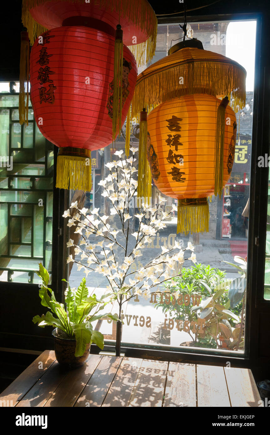 Late afternoon sun lights restaurant window in the ancient walled city of Pingyao, Shanxi Province, China. - Stock Image