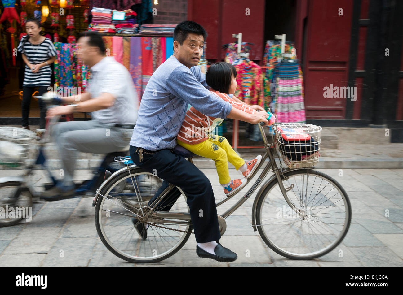 Young daughter shares bicycle with father in the ancient walled city of Pingyao, Shanxi Province, China. - Stock Image