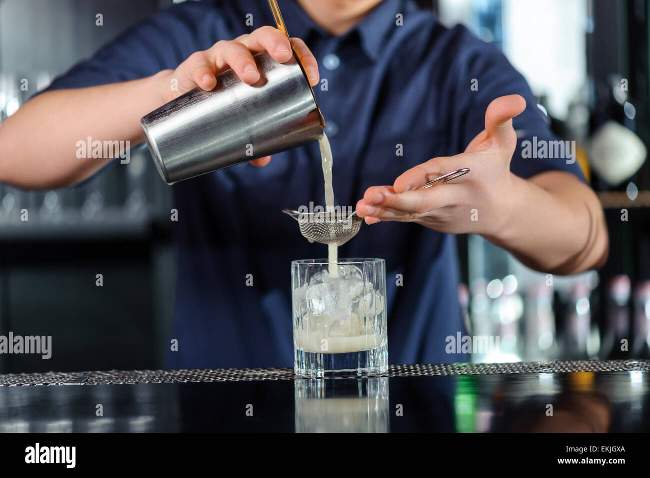 Barman makes cocktail in a bar - Stock Image