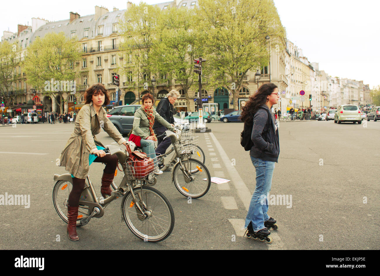 Cyclists and a skater on the street of Paris, France Stock Photo
